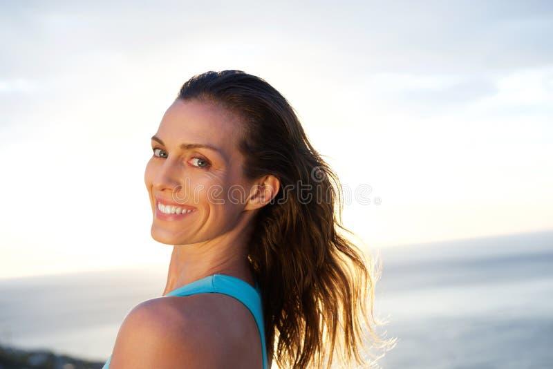 Frau, die über Schulter mit Meer im Hintergrund schaut lizenzfreie stockfotos