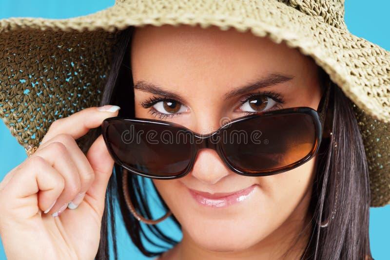 Frau, die über Sonnenbrille schaut stockbilder