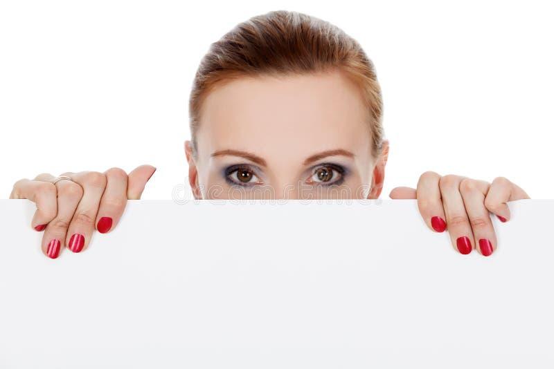 Frau, die über weißem Hintergrund schaut stockfotografie