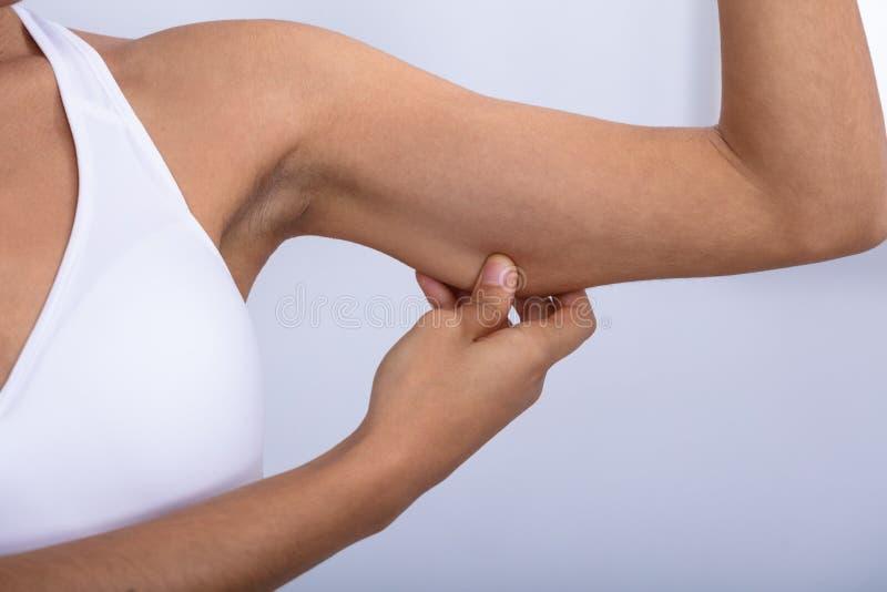 Frau, die ?berm??iges Fett auf ihren Armen ?berpr?ft stockbilder
