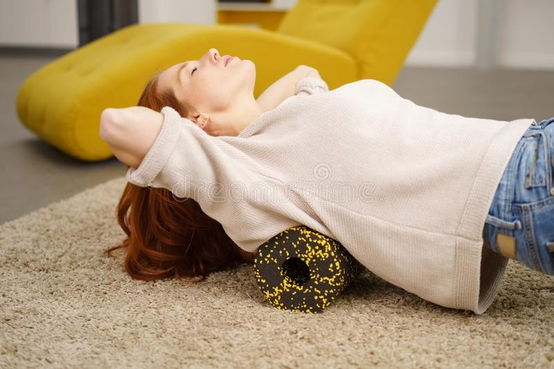 Frau, die Übungen auf Boden mit Schaumrolle tut stockbild