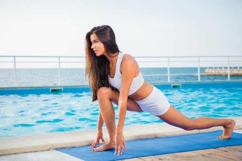 Frau, die Übungen auf Yogamatte ausdehnend tut lizenzfreie stockfotos
