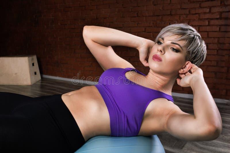 Frau, die Übungen mit fitball im Eignungssportunterricht tut Engagierende Kernbauchmuskeln Bildkonzept von gesundem stockfotografie