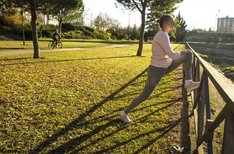 Frau, die Übungen am städtischen Park in der Herbstsaison ausdehnend tut stockbild
