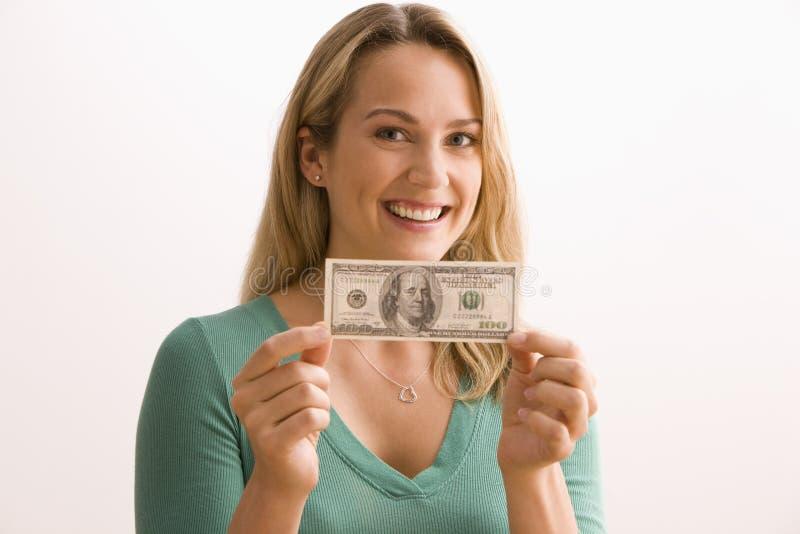 Frau, die 100 Dollarschein anhält stockfotografie