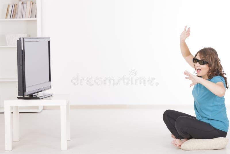 Frau, die 3D in den Gläsern fernsieht stockbilder
