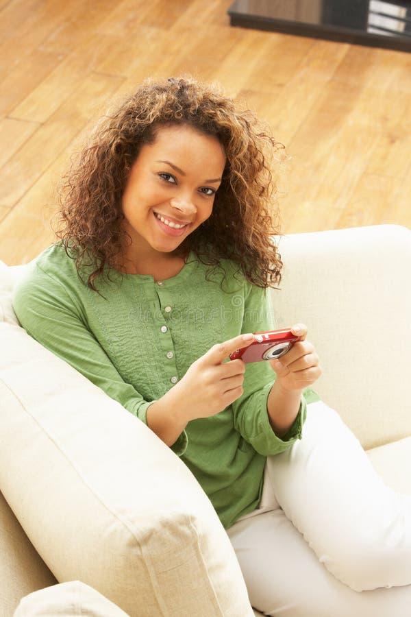 Frau, die Abbildungen auf Digitalkamera betrachtet lizenzfreies stockfoto