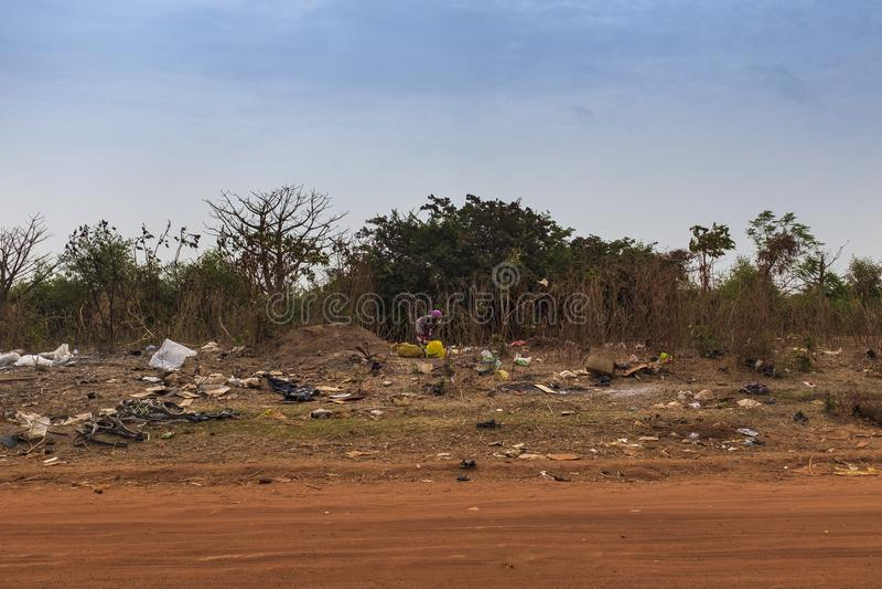 Frau, die Abfall in einer Müllgrube in den Stadtränden der Stadt von Bissau, in Guinea-Bissau, West-Afrika sammelt lizenzfreies stockbild