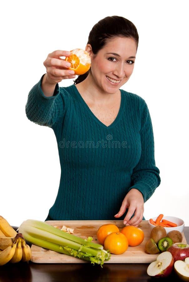 Frau, die abgezogene ornage Frucht darstellt lizenzfreie stockbilder