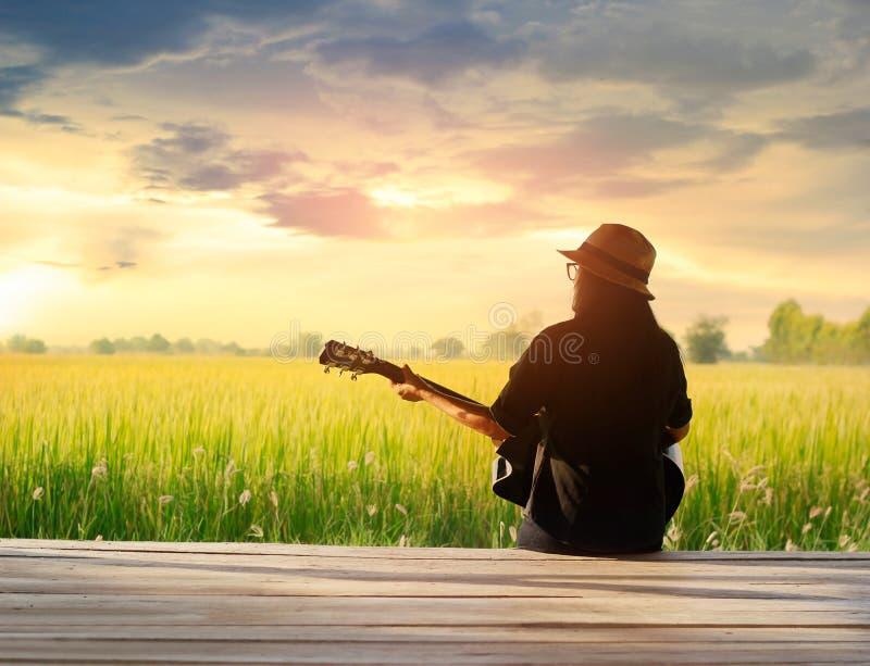 Frau, die Akustikgitarre auf dem ländlichen backgrou Sonnenuntergang des Feldes spielt lizenzfreies stockbild