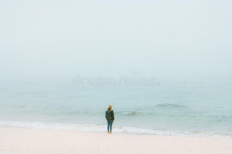 Frau, die allein auf dem Strand denkt mit nebeligem Meerblick steht lizenzfreie stockfotos