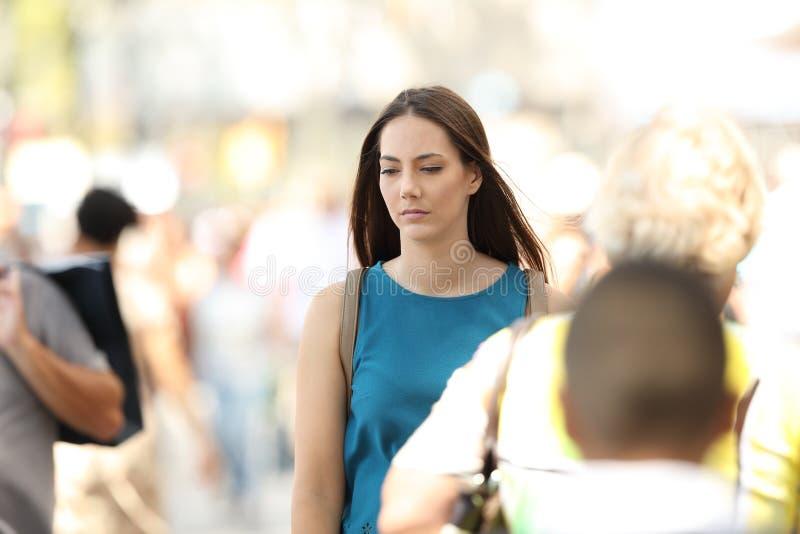 Frau, die allein glaubt, gehend zwischen Leute stockfotos