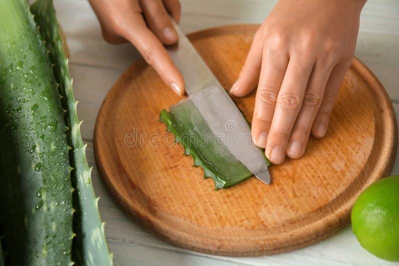 Frau, die Aloevera-Blatt auf hölzernem Brett, Nahaufnahme schneidet lizenzfreie stockfotos