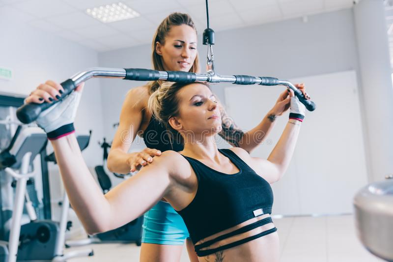 Frau, die anderer Frau mit ihrem Training hilft stockfoto