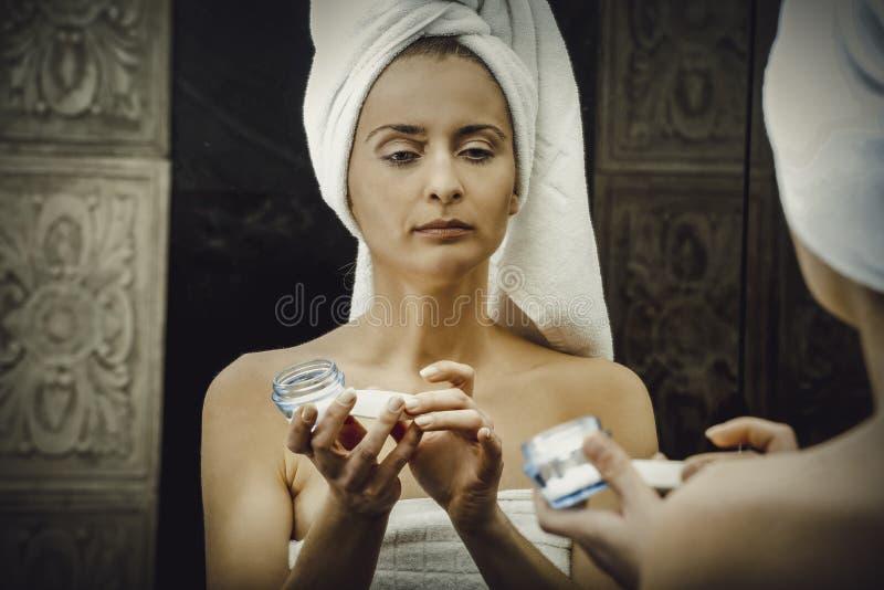 Frau, die Antialterncreme auf ihr Gesicht setzt lizenzfreies stockfoto