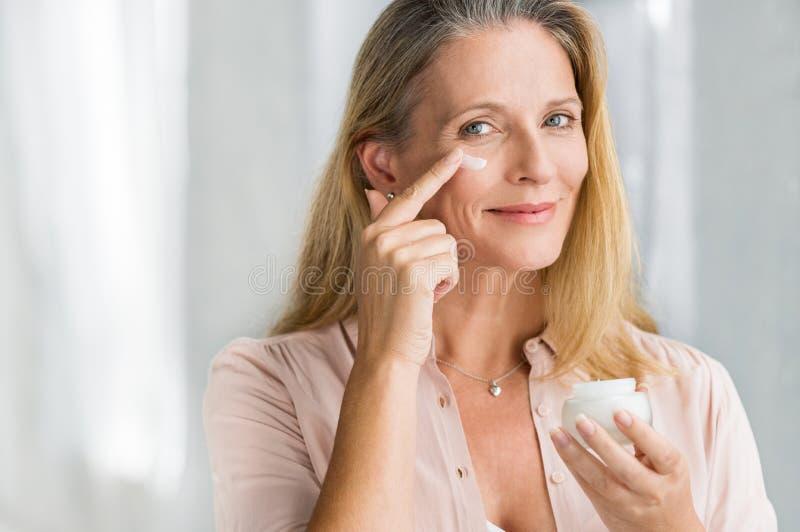 Frau, die Antialternlotion auf Gesicht anwendet lizenzfreies stockfoto