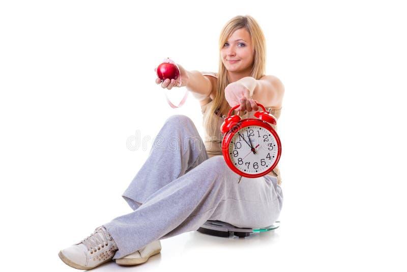 Frau, die Apfel, messendes Band und Uhr hält stockfotos