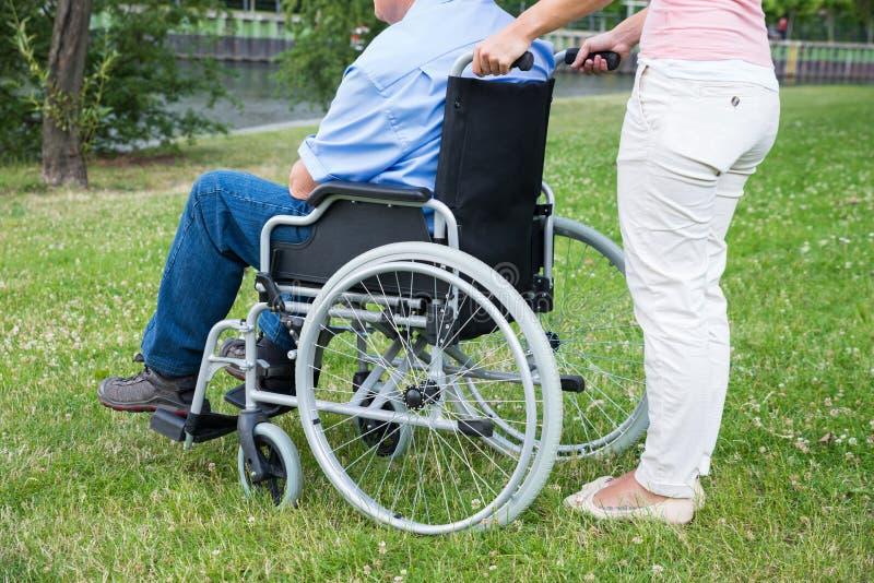 Frau, die arbeitsunfähigen Mann auf Rollstuhl unterstützt stockfotografie