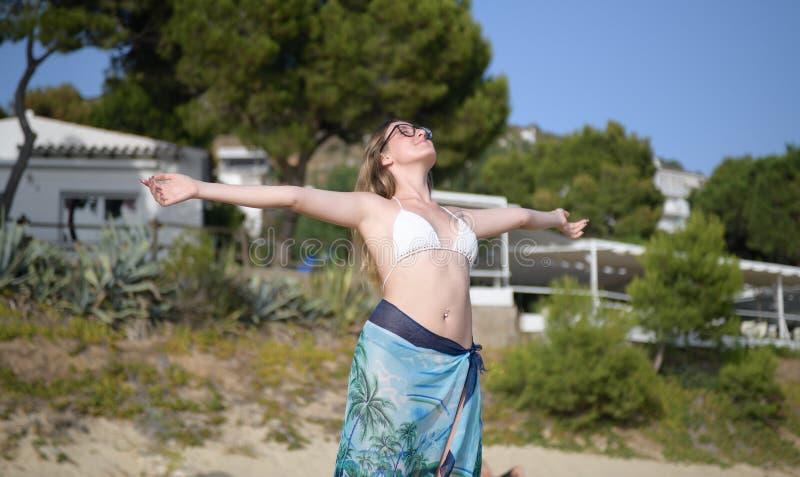 Frau, die Arme auf dem Strand atmet und ausdehnt lizenzfreies stockbild