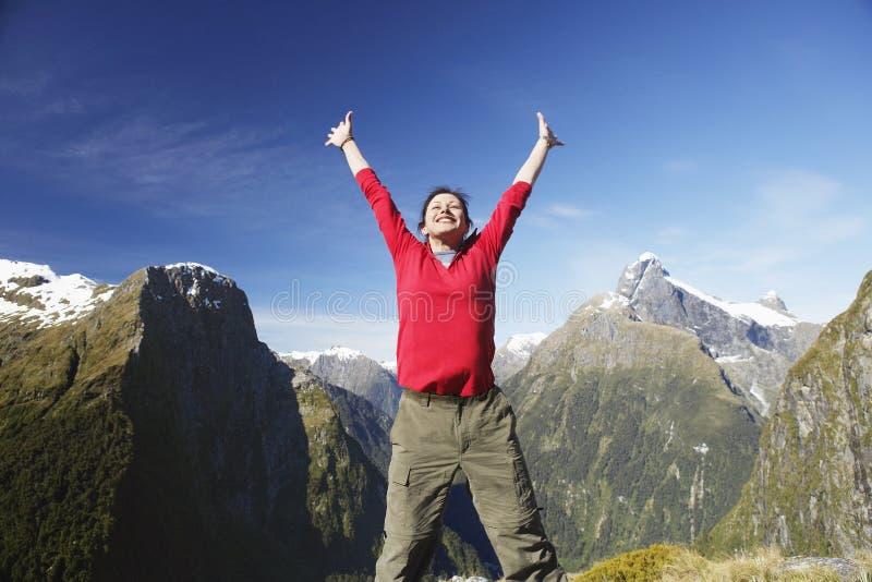 Frau, die Arme gegen Bergspitzen anhebt lizenzfreie stockbilder