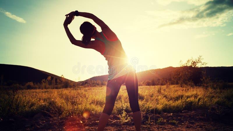 Frau, die Arme vor Lauf auf Sonnenuntergangwald ausdehnt stockbild