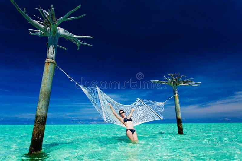 Frau, die auf Überwasser Hängematte sich lehnt lizenzfreie stockbilder