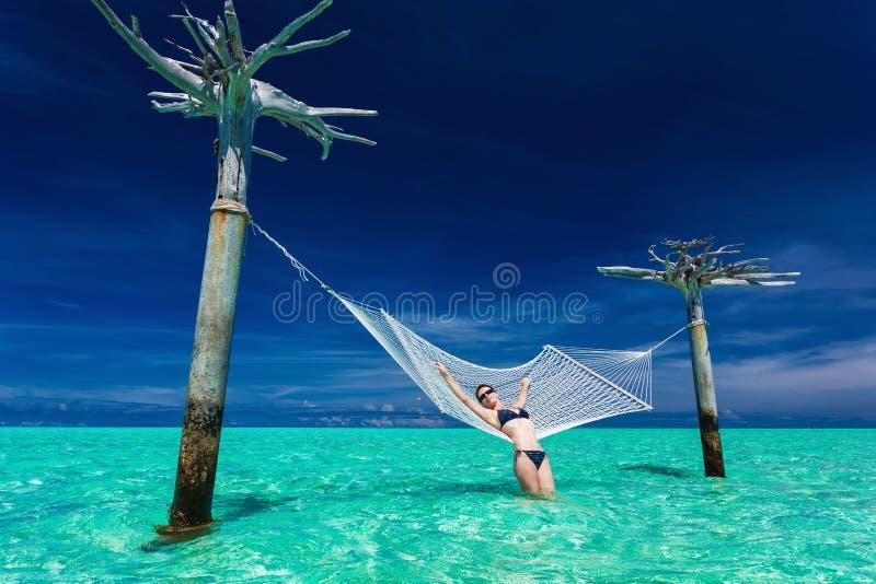 Frau, die auf Überwasserhängematte mitten in tropischem L sich entspannt stockfotografie