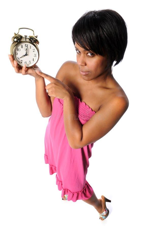 Frau, die auf Alarmuhr zeigt lizenzfreie stockfotografie