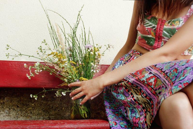 Frau, die auf alter hölzerner roter Bank mit rustikalem Blumenstrauß von wi sitzt lizenzfreies stockfoto