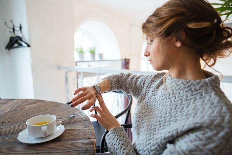 Frau, die auf Armbanduhr im Restaurant schaut lizenzfreies stockfoto
