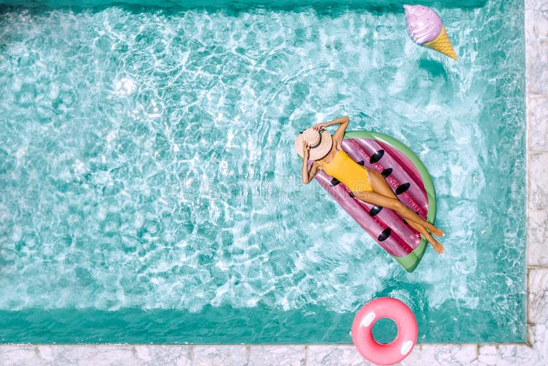 Frau, die auf aufblasbarem lilo im Hotelpool sich entspannt stockfoto