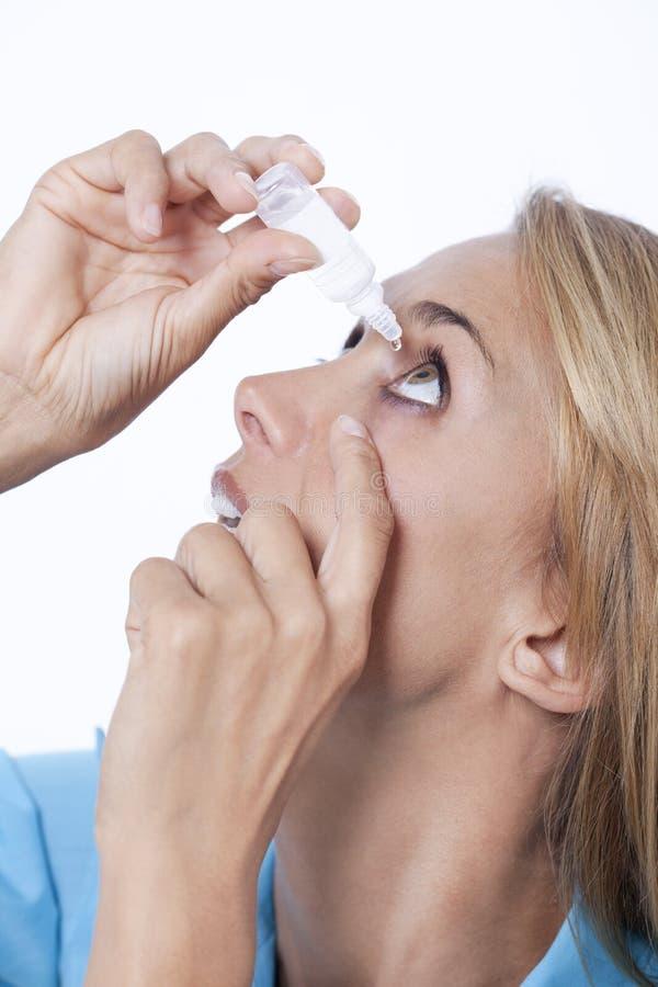 Frau, die auf Augentropfen sich setzt lizenzfreie stockbilder