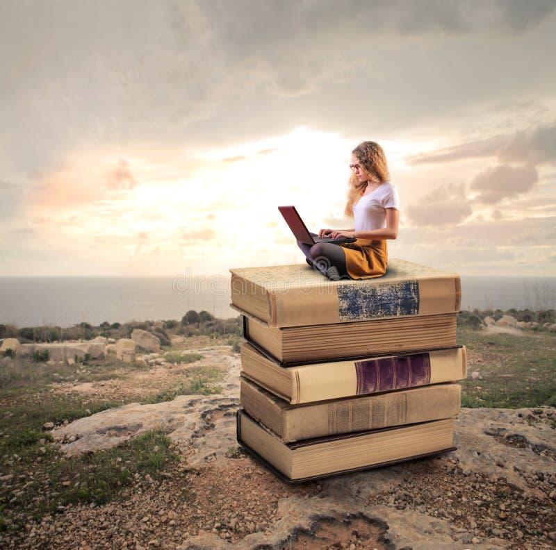 Frau, die auf Büchern sitzt stockfoto