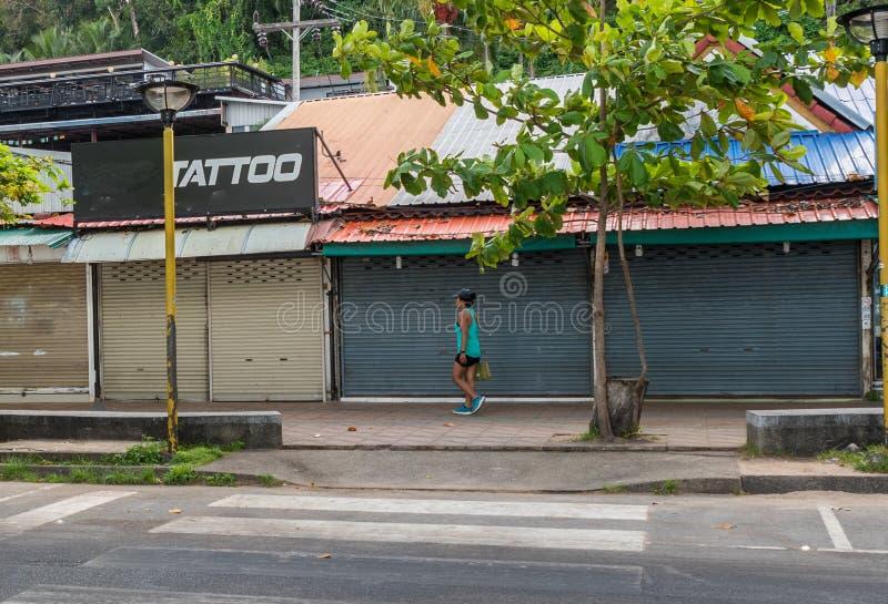 Frau, die auf Bürgersteig hinter zugänglichen Computerräumen geht stockbild
