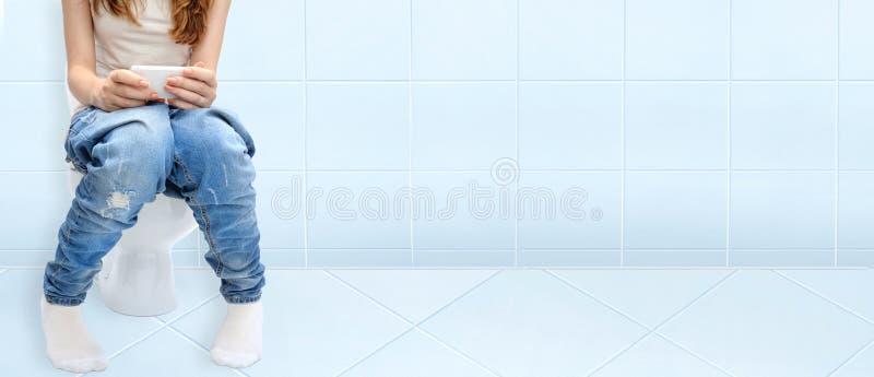 Frau, die auf Badezimmer- oder WC-Toilettenschüssel unter Verwendung des Telefons in den Händen sitzt stockfotos