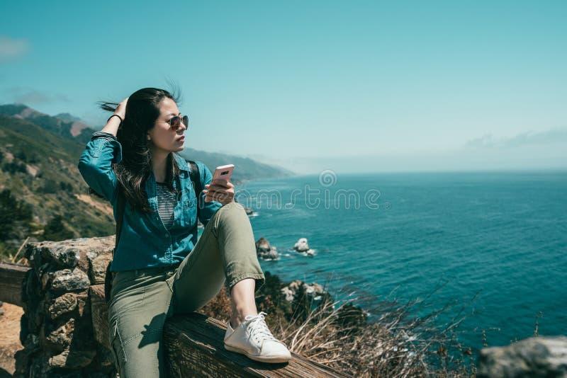 Frau, die auf Bank mit einem Beinverbiegen sitzt lizenzfreies stockfoto