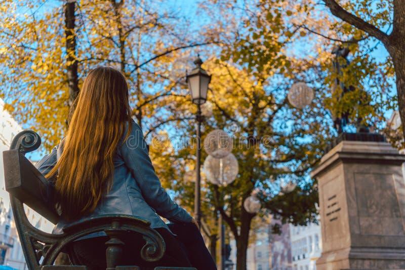 Frau, die auf Bank nach Spaziergang in der Fallstadt stillsteht stockfotos