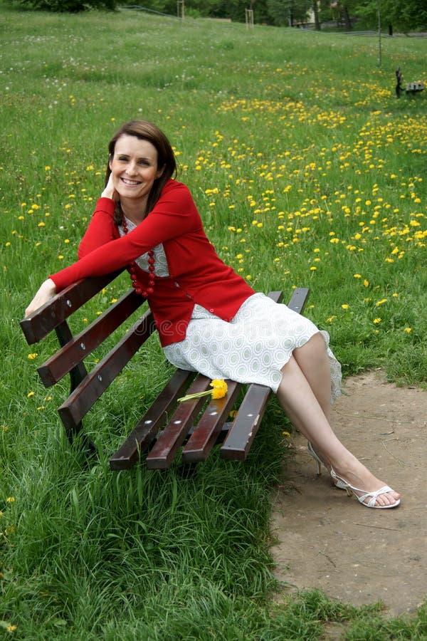 Frau, die auf Bank sitzt lizenzfreie stockfotografie