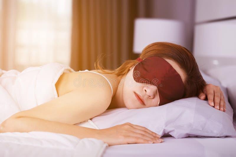 Frau, die auf Bett mit Augenmaske im Schlafzimmer mit weichem Licht schläft stockfoto