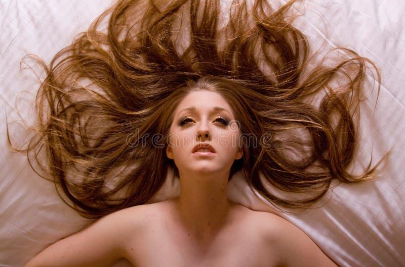 Frau, die auf Bett sich entspannt lizenzfreie stockfotografie