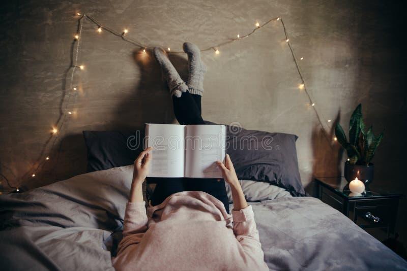 Frau, die auf Bett- und Lesebuch liegt lizenzfreie stockbilder