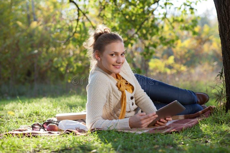 Frau, die auf Bettwäsche auf grünem Gras mit ipad liegt lizenzfreies stockfoto