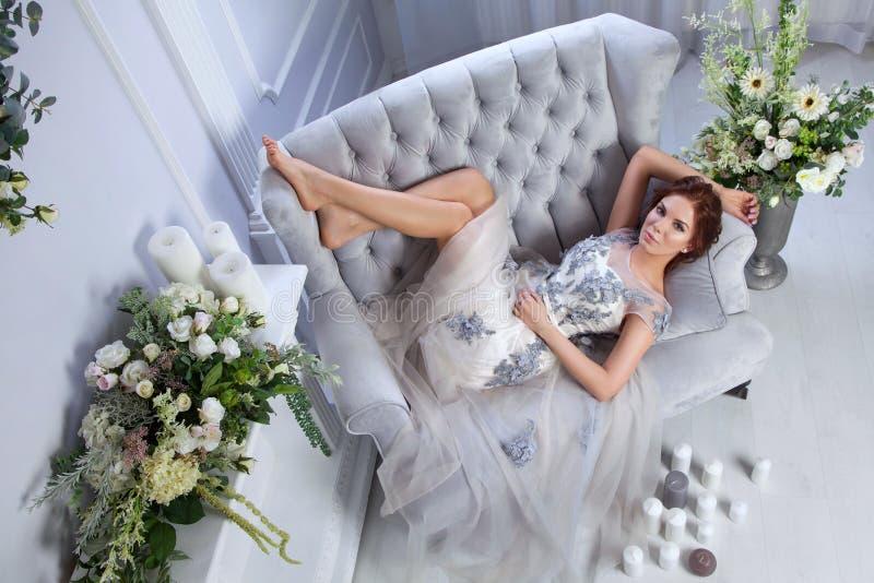 Frau, die auf blauem Sofa sich entspannt stockbilder