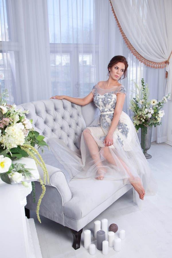 Frau, die auf blauem Sofa sich entspannt lizenzfreies stockfoto