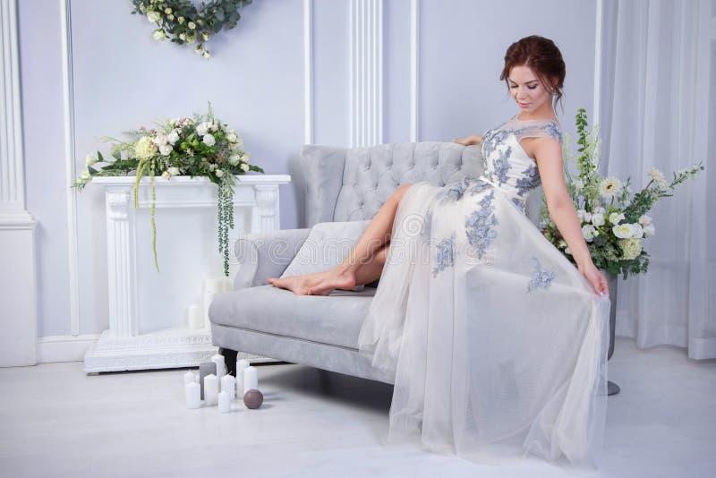 Frau, die auf blauem Sofa sich entspannt lizenzfreie stockfotografie
