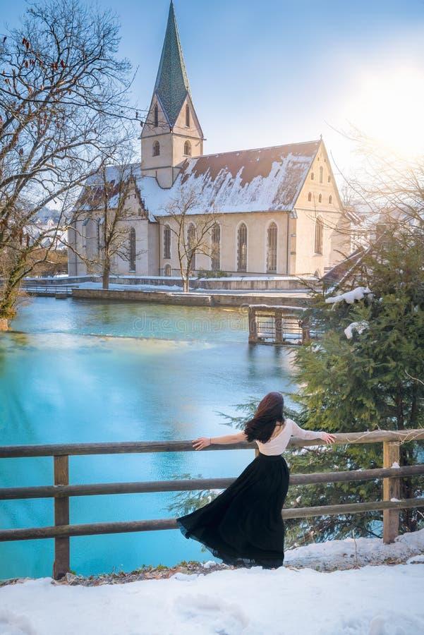 Frau, die auf blauem Wasser lakeshore meditiert stockbild
