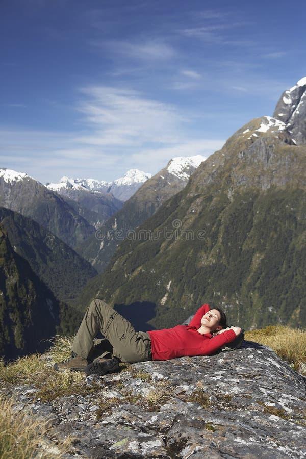 Frau, die auf Boulder gegen Berge liegt lizenzfreie stockfotografie