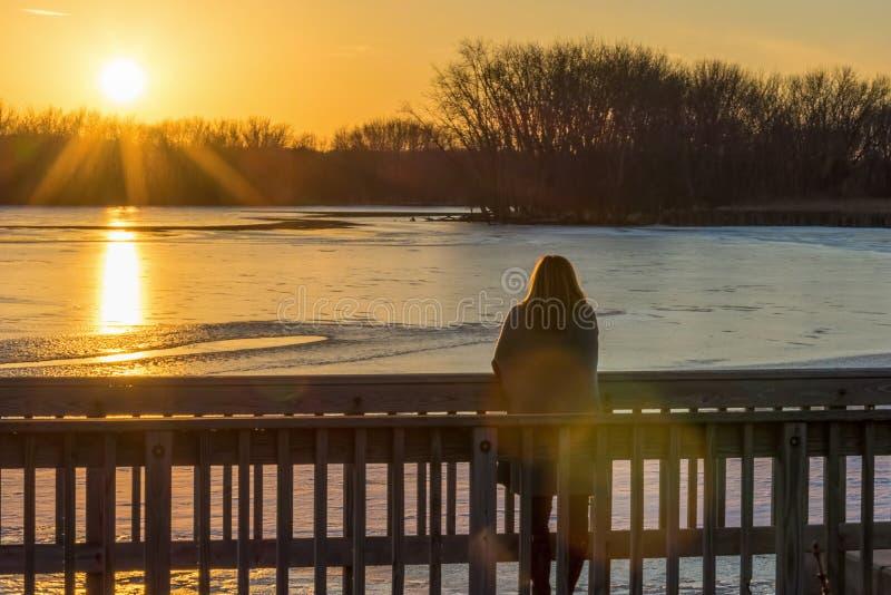 Frau, die auf Brücke über aufpassendem Sonnenuntergang des gefrorenen Flusses steht lizenzfreie stockfotos