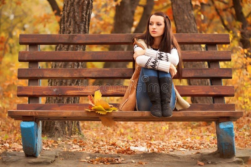 Frau, die auf brauner Bank sitzt stockbild