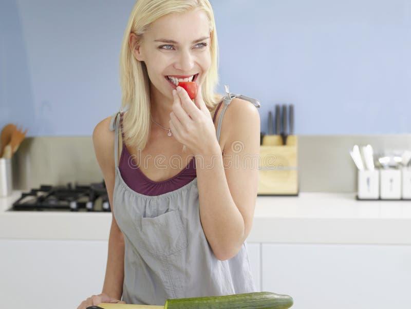 Frau, die auf Cherry Tomato eine Kleinigkeit isst stockbild